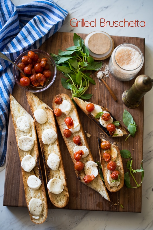Grilled Bruschetta Recipe with Mozzarella Cheese, basil and Tomatoes on a cutting board