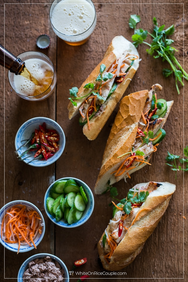 Platter of Vietnamese chicken banh mi assembly and glass of beer by whiteonricecouple.com