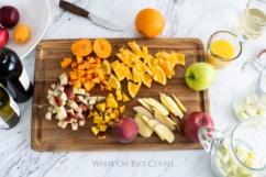 Tabla de cortar con fruta fresca picada para la receta de sangría de whiteonricecouple.com