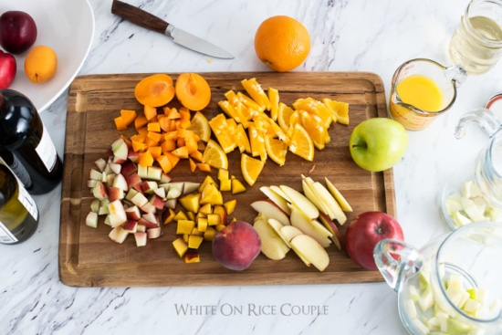 Cutting board with chopped fresh fruit for Sangria recipe from whiteonricecouple.com