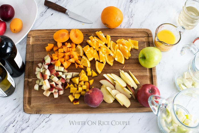 Cutting board with chopped fresh fruit for boozy punch recipe from whiteonricecouple.com