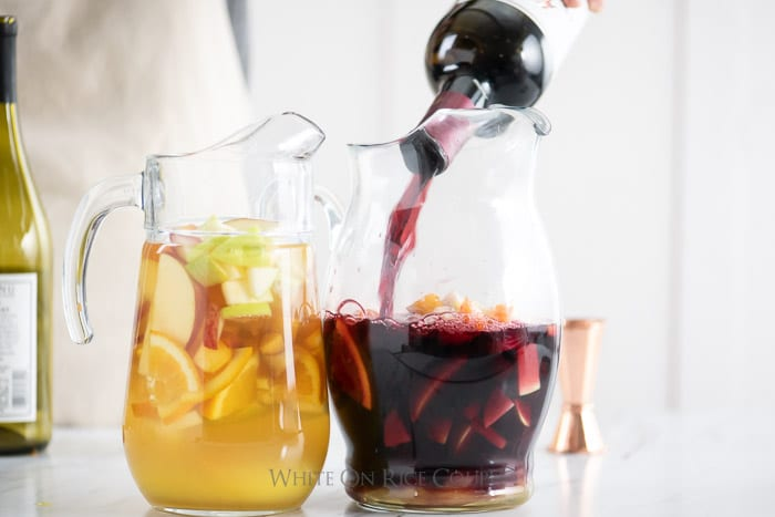 Pitcher of fruit with red wine pouring into the pitcher for sangria by whiteonricecouple.com