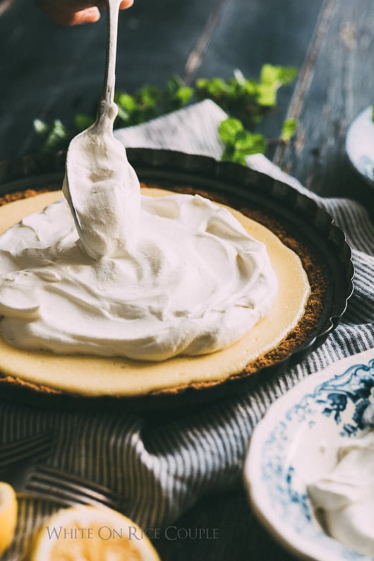 Meyer Lemon Pie with whipped cream being spread over the pie