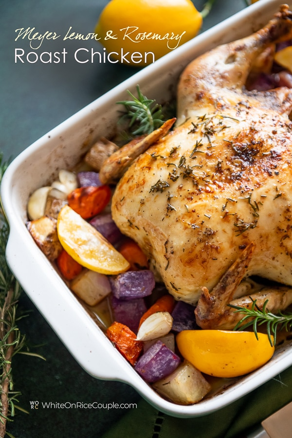 Lemon herb roast chicken recipe with fresh herbs and lemon in a baking dish close up