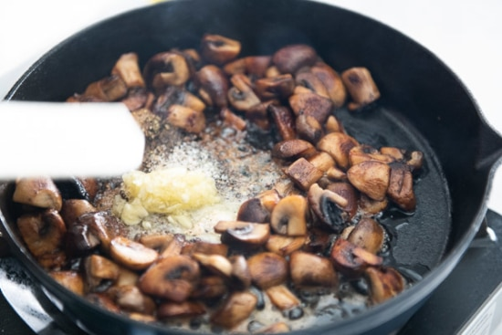 Garlic and butter added to skillet of mushrooms