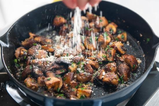 Parmesan being sprinkled on mushrooms