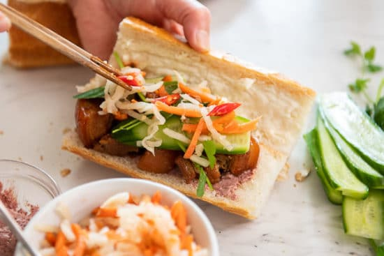 Adding caramel pork and pickled daikon to baguette sandwich