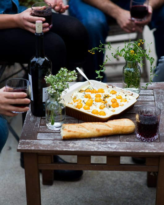 Baked tomato goat cheese dip with ricotta cheese in a serving dish on a table