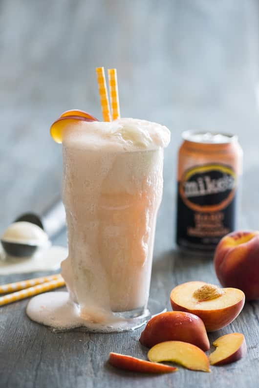 Boozy Peaches-n-Cream Ice Cream Float with Mike's Hard Peach Lemonade in a glass cup