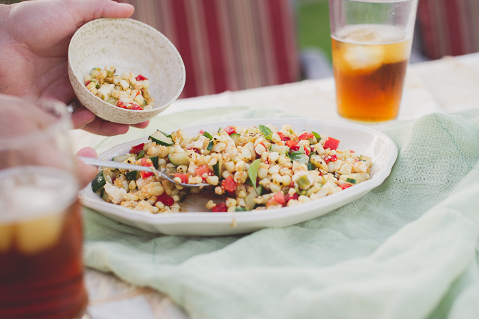 Fire Roasted Summer Corn Salad scooping into a bowl