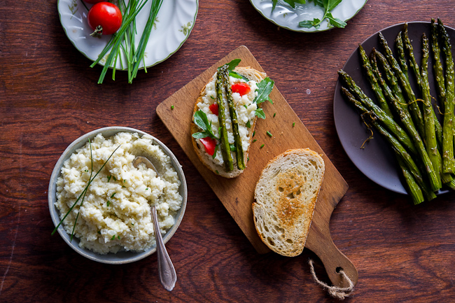 Smashed cauliflower sandwich recipe with roasted asparagus on a cutting board