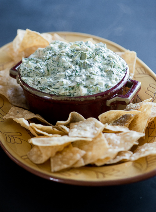 stove top Artichoke Spinach Dip on a platter with tortilla chips
