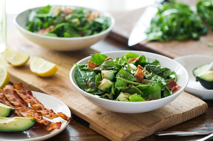 Bacon Spinach Salad with Amazing Avocado Vinaigrette in a bowl
