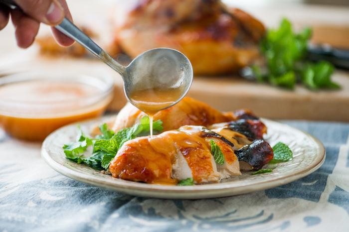 Sriracha Roast Chicken Recipe with Sriracha Gravy pouring over cut chicken