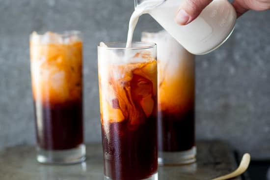 Adding half and half to chilled thai tea in a glass with ice